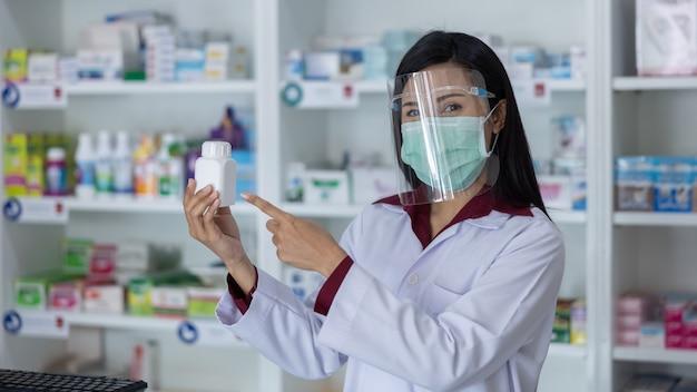 Farmacista di donne professionali asiatiche con visiera protettiva sul viso lavorando in farmacia moderna e mostrando la bottiglia di medicina bianca in mano al negozio di farmacia thailandia