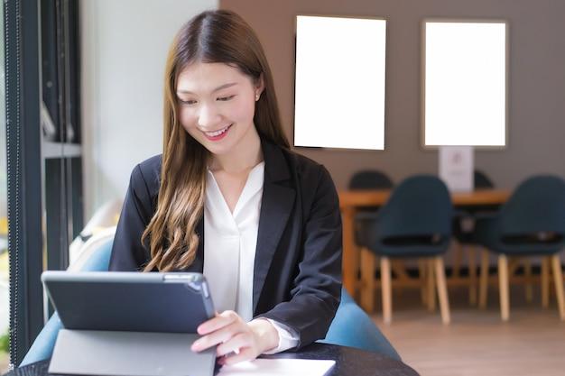 La donna lavoratrice professionista asiatica in abito nero sta lavorando su un tablet sul tavolo sorridendo felicemente in ufficio e lavorando a casa.