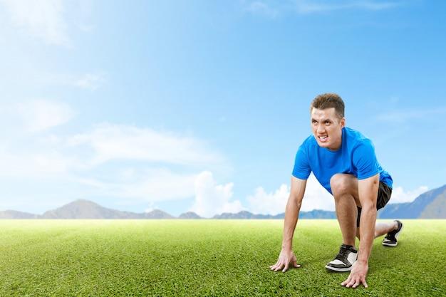 Uomo asiatico del corridore pronto a funzionare sul campo di erba
