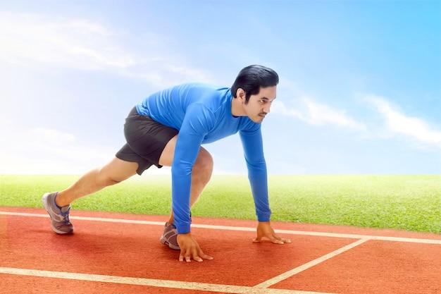 Uomo asiatico del corridore pronto a correre sulla pista corrente