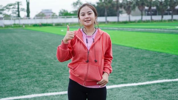 Donna asiatica del corridore che indossa giacca e auricolare gesto ok