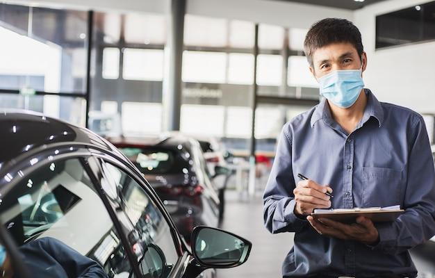 Il venditore asiatico indossa la maschera chirurgica che lavora nell'ispettore che controlla la scrittura negli appunti nel garage della concessionaria