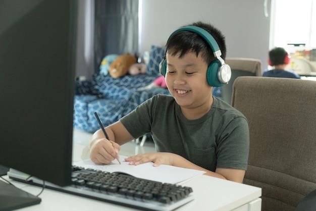 Ragazzo di scuola asiatico che mostra il divertimento durante il corso di apprendimento online durante la scuola a casa