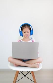 Ragazza asiatica della scuola che si siede sulla sedia facendo uso della classe di apprendimento in linea di studio della cuffia dal computer portatile