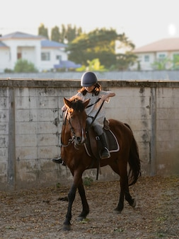 Ragazza del bambino della scuola asiatica con cavallo, equitazione o pratica di equitazione al ranch di cavalli.