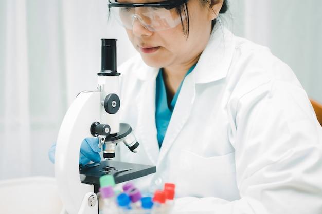Scienziato asiatico biochimico ricerca di lavoro con un microscopio in laboratorio per proteggere il coronavirus covid-19.