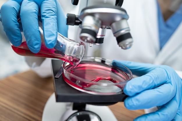 Ricerca scienziato asiatico con un microscopio.