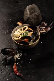 Zuppa di pesce asiatica con cozze, polpo, anelli di calamari, tagliatelle, semi di sesamo e peperoncino essiccato