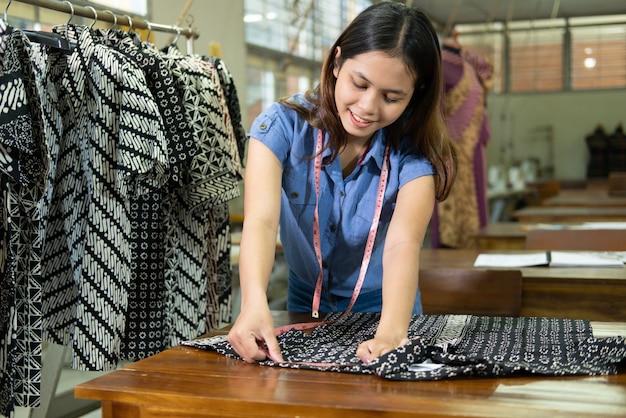 Le sarte asiatiche misurano i vestiti con un righello secondo le regole nella stanza di produzione