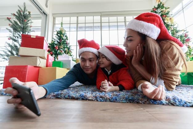 Smartphone asiatico della tenuta di selfie che prende l'immagine. felice giovane famiglia con bambini che si divertono a celebrare il natale. periodo natalizio. mio padre, mia madre e mia figlia con i cappelli di babbo natale mentono davanti a una confezione regalo a casa.