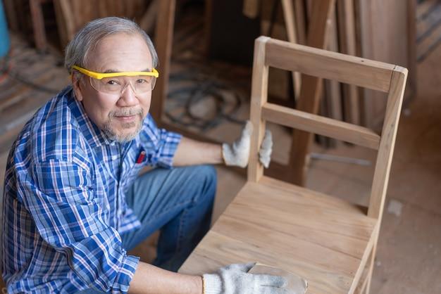 Uomo asiatico anziano falegname che leviga la superficie su mobili per sedie in legno presso l'officina di falegnameria