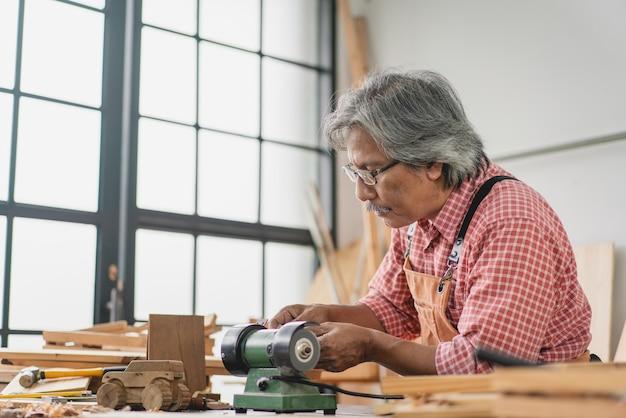 L'uomo anziano asiatico del carpentiere che per mezzo della piccola macchina della smerigliatrice fa l'automobile di legno all'officina