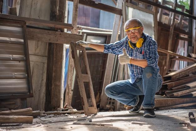 Il carpentiere senior asiatico mostra i pollici in su i vecchi telai delle finestre per il rinnovo presso il laboratorio di falegnameria