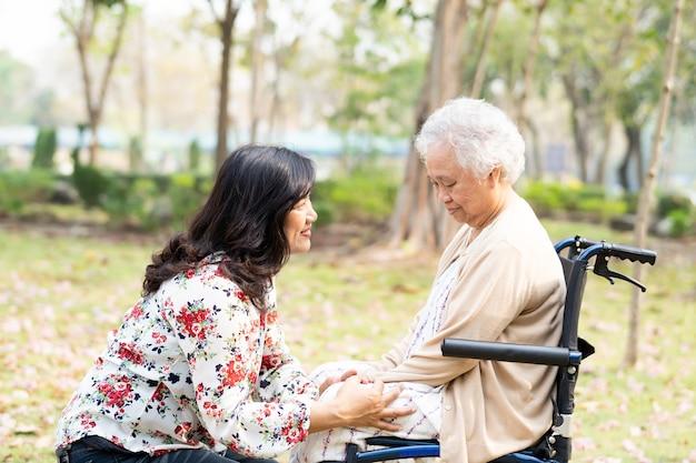 Paziente asiatico anziana o anziana donna anziana con cura, aiuto e supporto felice su sedia a rotelle nel parco in vacanza, concetto medico sano e forte