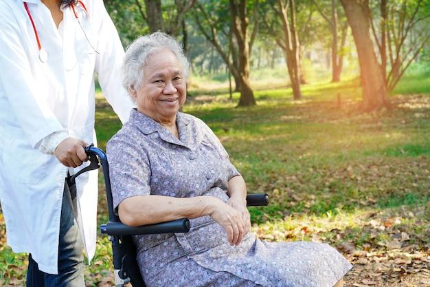 Paziente asiatico o anziano della donna della signora anziana con cura, guida e supporto sulla sedia a rotelle in parco in vacanza
