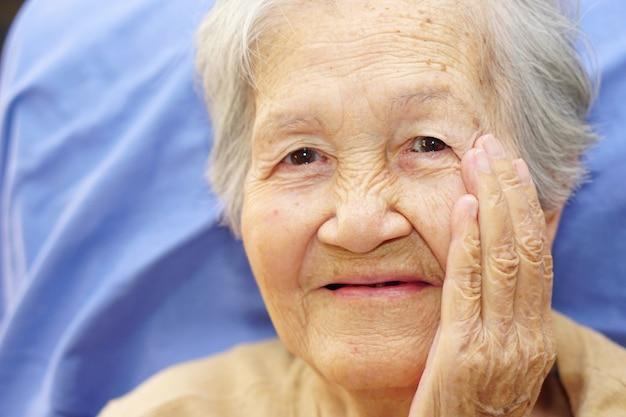 Donna anziana senior o anziana asiatica della signora che sorride con la mano che tocca sul suo fronte. concetto medico, felice e ritratto.