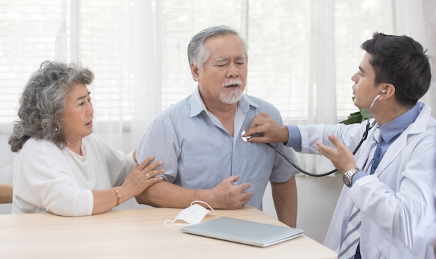 Uomo anziano anziano senior asiatico con la maschera sulla menzogne sul sofà mentre il giovane medico caucasico si siede sul controllo del ginocchio il suo battito cardiaco