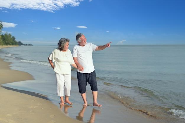 Le coppie asiatiche di amore senior viaggiano sulla spiaggia. famiglia in età di pensionamento rilassante e ricreativa durante le vacanze estive.