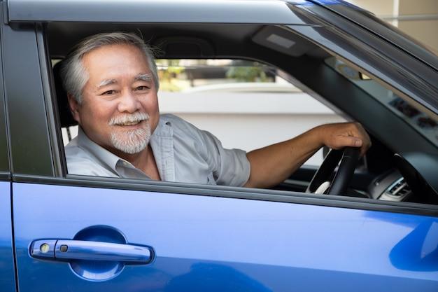 Uomo anziano asiatico alla guida di un'auto e sorridere felicemente con felice espressione positiva durante il viaggio verso il viaggio, la gente si diverte a ridere nel trasporto e guida attraverso il concetto