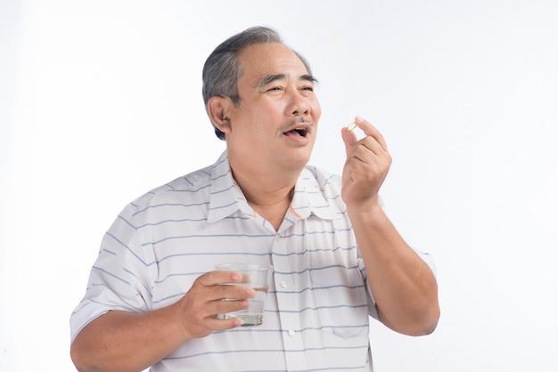 Uomo anziano asiatico che tiene la capsula di omega-3 isolata su white