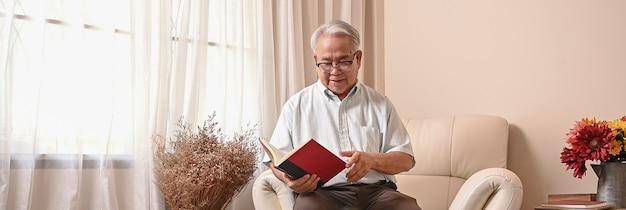 Libro di lettura dell'uomo anziano asiatico e stare da solo a casa. stile di vita in età pensionabile.