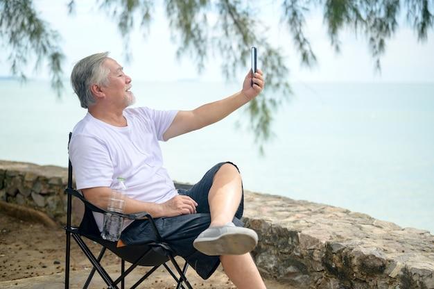 Uomo anziano asiatico seduto accanto alla spiaggia da solo. età pensionabile tramite cellulare per videochiamare con la famiglia.