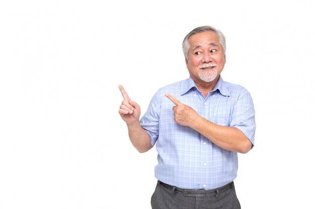 Uomo senior asiatico che sorride e che indica lo spazio vuoto della copia isolato sulla parete bianca