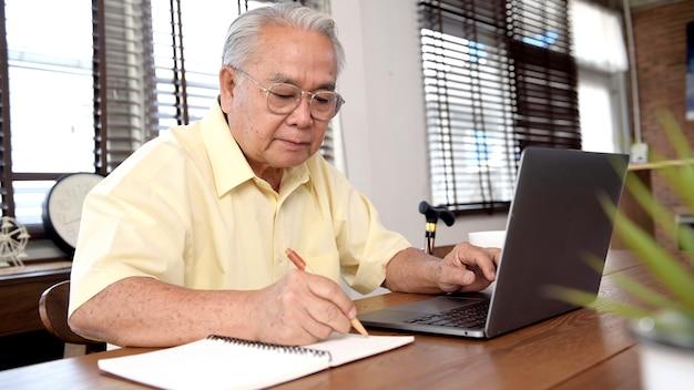 Uomo anziano asiatico che utilizza laptop e cerca un'assicurazione dopo il pensionamento. il nonno resta solo a casa.