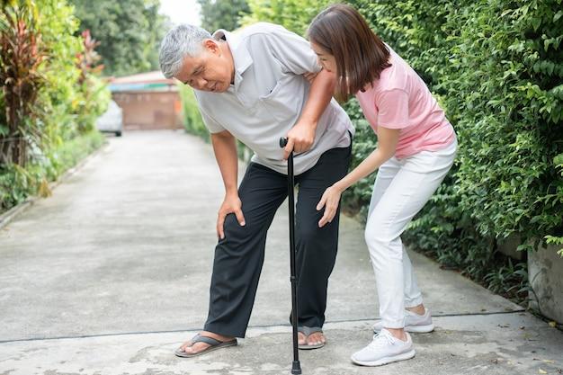 Uomo anziano asiatico che cammina nel cortile e infiammazione dolorosa e rigidità delle articolazioni artrite