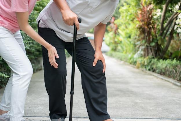Uomo maggiore asiatico che cammina nel cortile e infiammazione dolorosa e rigidità delle articolazioni