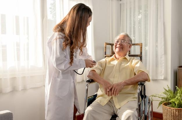 L'uomo anziano asiatico era malato e seduto su una sedia a rotelle. il medico controlla la salute in età pensionabile a casa.