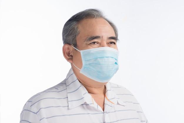 Uomo anziano asiatico con maschera facciale isolata su white