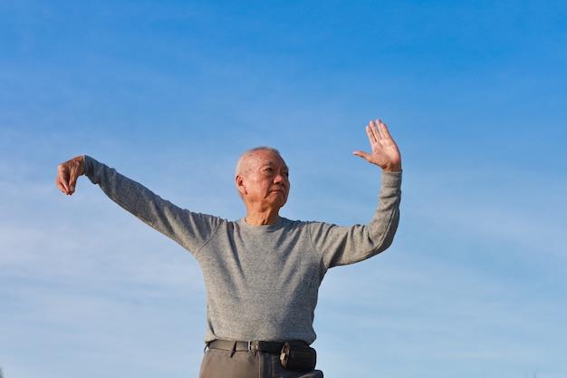 L'uomo anziano maggiore asiatico pratica il kungfu cinese di taichi sulla spiaggia