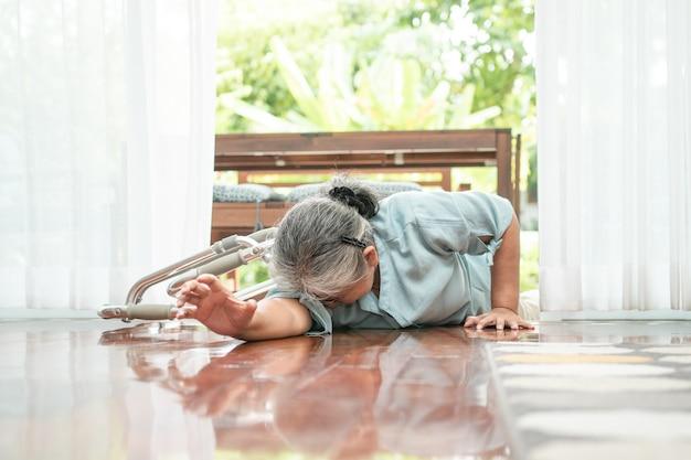 Donna maggiore asiatica che cade sul pavimento di menzogne a casa dopo inciampato alla porta