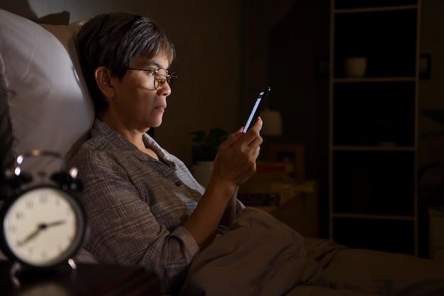 Donna maggiore asiatica che ha gli occhi irritati e stanchi quando utilizza lo smartphone mentre giaceva a letto di notte