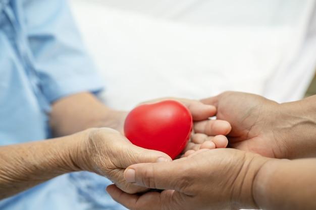 Donna anziana asiatica paziente con cuore rosso in mano sul letto in ospedale in