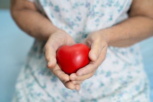 Paziente asiatico della donna maggiore che tiene cuore rosso.