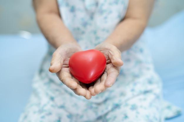 Paziente asiatico senior della donna che tiene cuore rosso.