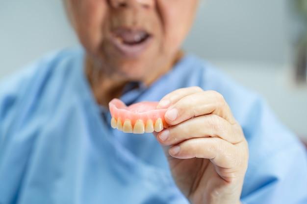 Paziente asiatico della donna senior che tiene per usare la protesi dentaria in ospedale.