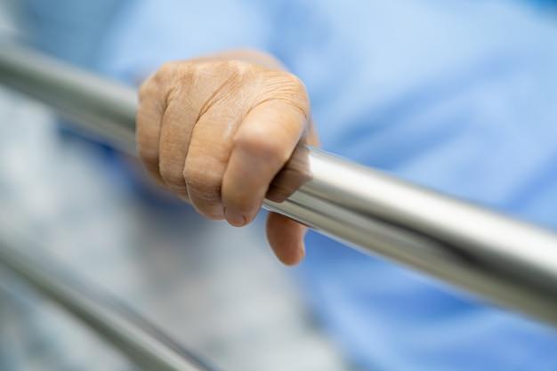 Il paziente asiatico della donna senior si sdraia per gestire il letto ferroviario in ospedale.