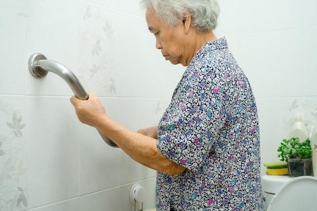 Il paziente asiatico della donna senior usa la sicurezza della maniglia del bagno della toletta.