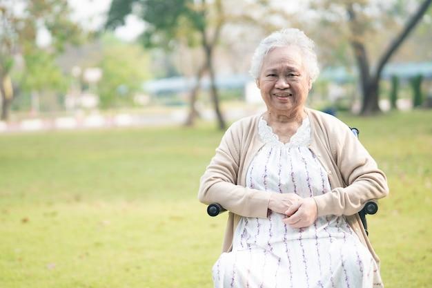 Paziente senior asiatico della donna sulla sedia a rotelle in parco.