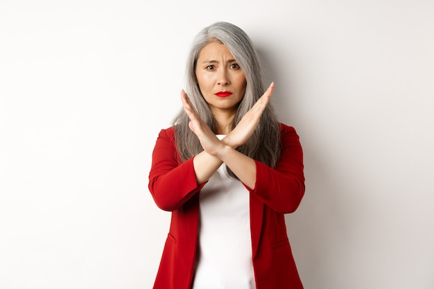 Donna anziana asiatica in blazer rosso che fa un gesto incrociato, supplicando di fermarsi, non essere d'accordo e disapprovare qualcosa, in piedi su sfondo bianco