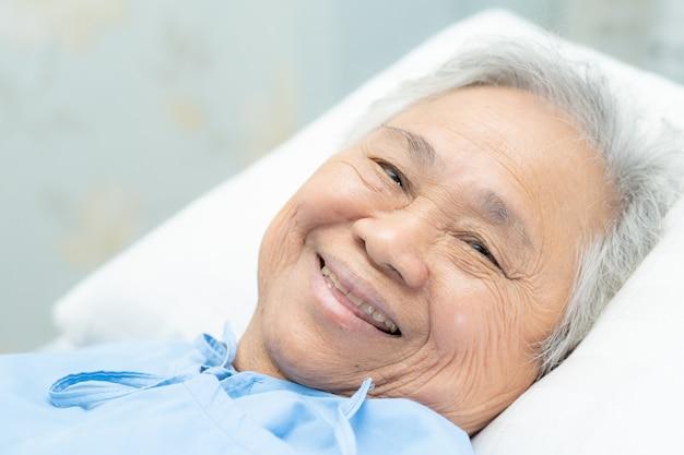 La donna senior asiatica sorride sull'ospedale