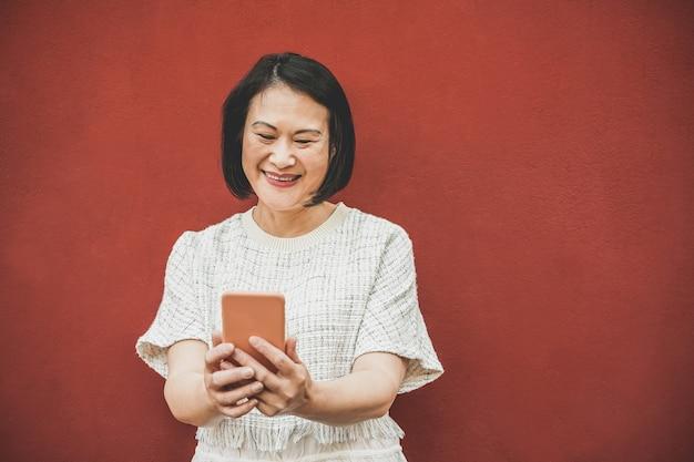 Donna senior asiatica che usando app dello smartphone - femmina cinese matura divertendosi con la tendenza della tecnologia