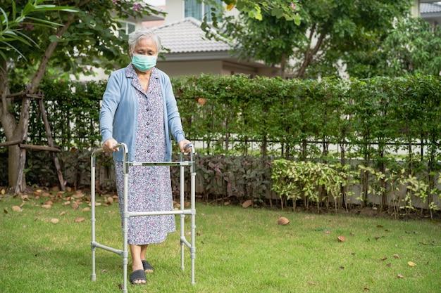 La donna anziana asiatica cammina con il deambulatore e indossa una maschera per proteggere il coronavirus covid-19.