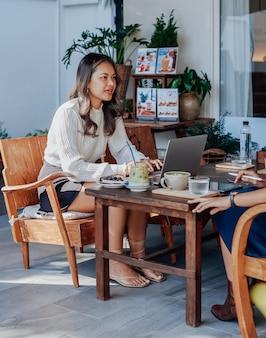 Una donna d'affari asiatica seria discute di qualcosa con il suo collega seduto al tavolo fuori e usa un computer portatile al bar.