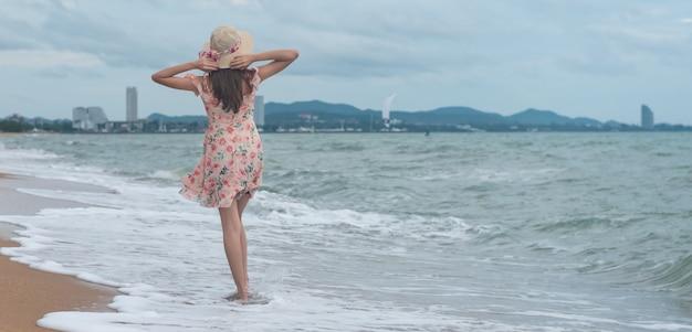 Donna sexy asiatica sulla spiaggia, viaggio di viaggio di vacanze estive, insegna con lo spazio della copia.