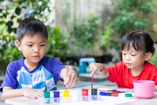 Bambini di pari livello asiatici che disegnano e che dipingono i colori sulla carta nella stanza.