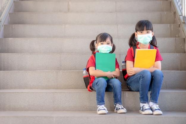 Fratello asiatico con maschera facciale che torna a scuola dopo la quarantena e il blocco del covid-19